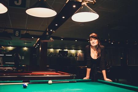 tetona: Mujer tetona hermosa morena joven que juega el billar en el vector rojo en el interior. la imagen en tonos. ambiente cálido.