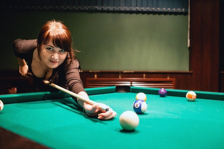cue sticks: Beautiful young busty brunette woman playing billiard on red table indoors. Toned image. Warm atmosphere. Stock Photo
