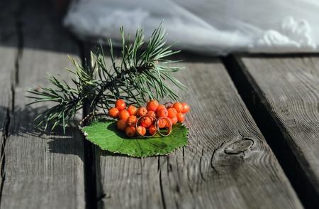 Rowan berries and wedding rings on vintage wooden boards.