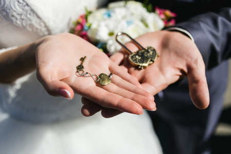 coulomb: Decorative wedding lock and keys with coulomb in hands of newlyweds.