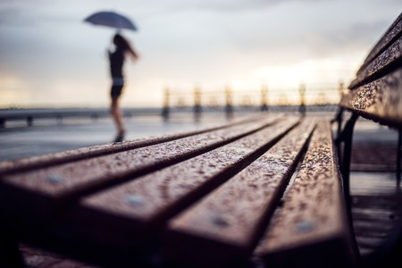 umbrela: Wet bench and silhouette woman with umbrela. Rainy weather concept Stock Photo