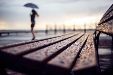 umbrela: Wet bench and silhouette woman with umbrela. Rainy weather concept Stock Photo