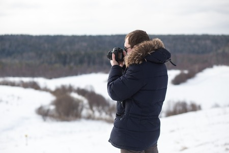 Photographer photographing winter panorama in hilly plain Stock Photo