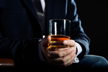 privilege: Closeup of serious businessman holding glass of whisky illustrate executive privilege concept.