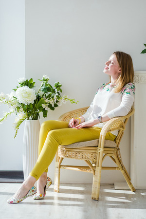 Pretty positive young blonde woman in casual white jacket and yellow trousers sitting on chair against light background.