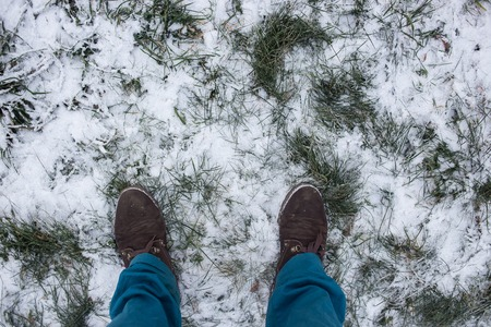 adult footprint: Male Boots In Winter Grass Under Snow. Stock Photo