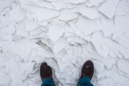 hiking boots: Hiking boots on river cracked ice, top view. Concept of danger of an exit to weak ice
