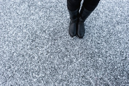 gritty: Women black leather boots standing on rough snow background. Gritty snow covered asphalt surface. Textplace. Top view