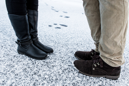 gritty: Male and Female casual boots standing on asphalt covered gritty snowY surface. Rough snowy surface. Textplace. Cold Winter. Side view.