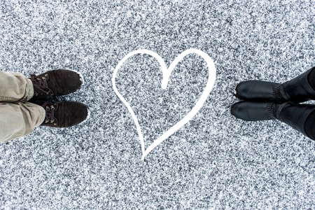 gritty: Men and womens boots standing at abstract heart symbol on asphalt covered gritty snow surface. Rough snowy. Cold Winter. Top view. Relations concept Stock Photo
