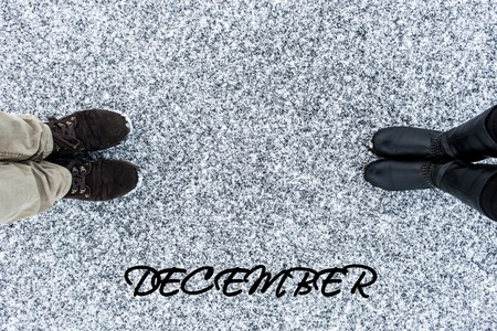 gritty: Male and Female boots standing at heart symbol with text december on asphalt covered gritty snow surface. Rough snowy. Winter love. Top view. Relations concept