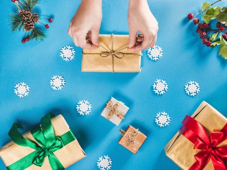 lay: Concept of Christmas items on a bright blue background. Womans hands wrapping Christmas gift. Flat lay of Christmas decorations, snowflakes, berries and twigs with presents Stock Photo