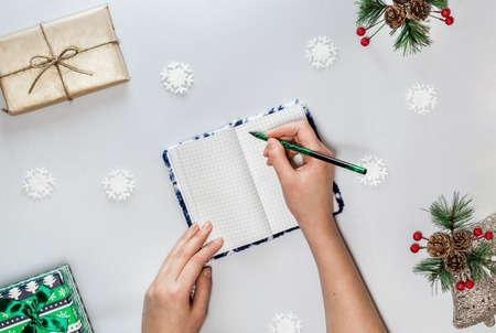 Christmas composition with notebook, female hands with green pencil small green box, snowflakes and spruce branch with red berries and cones. Concept christmas, new year plan. Flat lay. Light gray background