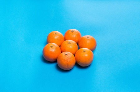 Sun symbol from Six Colorful fresh orange mandarins laid out on blue table viewed from above with copy space. Stock Photo