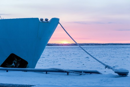 frozen ship cable under snow, bollard at the pier in winter. Stock Photo