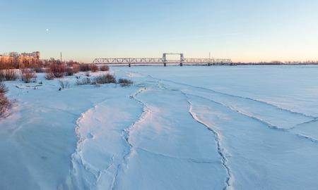 urbanism: Frozen river Northern Dvina and Railway bridge in Arkhangelsk, Russia. Winter shot