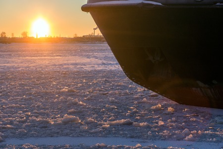 Icebreaker in the river ice on winter sunset. Nose of ship Stock Photo