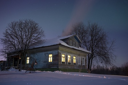 dacha: Old russian village house in the bitter cold. Winter night landscape with snow, stars, smoke from furnace and warm light from windows