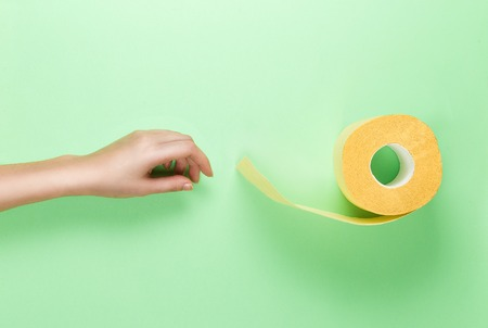Female Hand Reaches for Yellow Toilet Roll on Green Background. Flat lay glamour colours.. Top View. Banco de Imagens