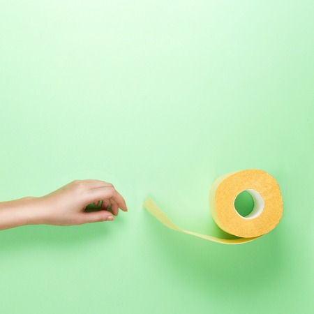 Female Hand Reaches for Yellow Toilet Roll on Green Background. Flat lay glamour colours.. Top View. Square crop.
