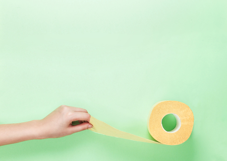 Female Hand Hold Yellow Toilet Paper Roll on Lime Green Background. Top View. Copy Space. Hygienic trendy fresh colored concept. Place text.