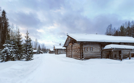 Old Village Log Houses in museum Small Karelians near Arkhangelsk, Russia. Winter time Archivio Fotografico