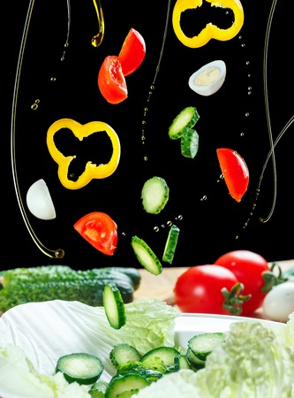 Vliegende ingrediëntensalade die op een zwarte achtergrond wordt geïsoleerd. Salade zwevend in de lucht boven de tafel. Slagroenten, kwartelseieren en olijfolie.