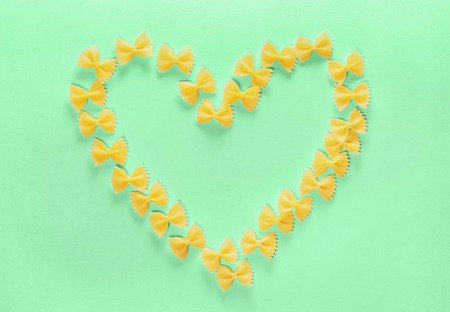 Heart Frame from Wwheat Pasta Farfalle on Green Background. Valentines Day or Mothers Day. Stock Photo