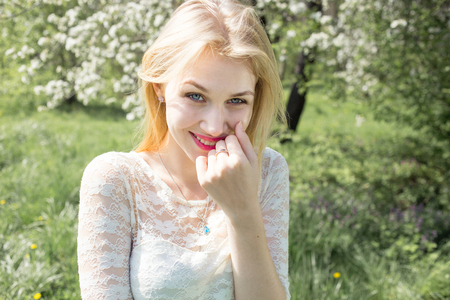 Cute smiling blonde woman beauty portrait, perfect fresh skin and healthy white smile, perfect basic makeup, rose lips, long lluttering hair. She clothed in lacy white dress Outdoor in blooming spring park
