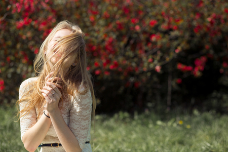 Young blonde woman enjoying aroma blooming garden in the air. Her eyes are closed from pleasure.