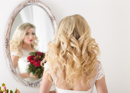 Beautiful curly haired bride in a wedding dress at a mirror in white room. Girl repeats the hairstyle and .