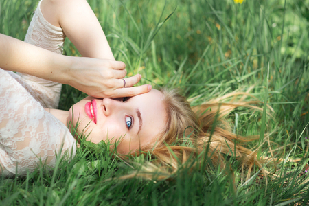 bright eyed: Cute Blue-eyed Blonde Lying on the Spring Grass. Happy young Woman with Red Lips and Natural Make Up in White Lacy Dress Having Fun in Spring Garden. Stock Photo