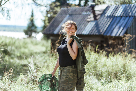 Young beautiful country woman in camouflage outfit discovering nature in the forest village with mosquito net. Travel lifestyle fashion concept. Stock Photo