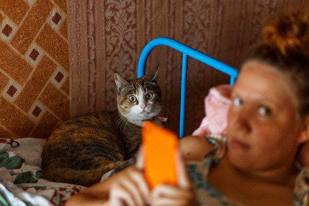 Funny picture of cat and the girl with astonishment look in the camera. Surprise.