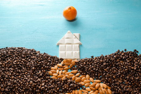bean family: The house from white chocolate, the earth from coffee grains, the road from almonds, the sun from a citrus on blue background. Abstract symbols flat lay composition. Concept of realty, cosiness, comfort, happy family etc.