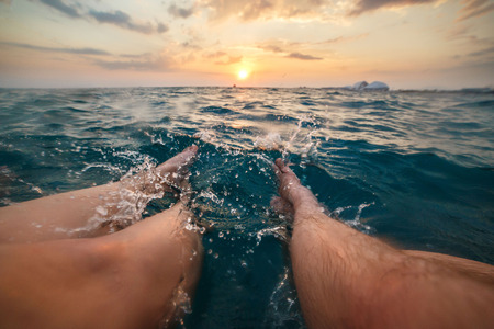 footcare: Image of female and male legs splashing aquamarine sea water on sunset. Colofur picture, selective focus. Stock Photo