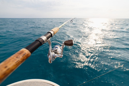 Fisherman fishing rod on the sunset close up. Opened sea.