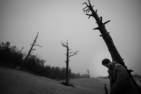 leaned: Man with the hung head has leaned the elbows on a dead tree.
