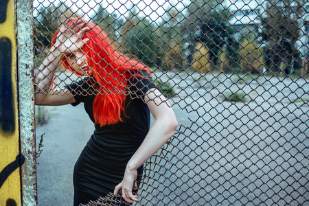 black hole: Fashionable redhead woman holding torn grid. Cold toning urban picture.
