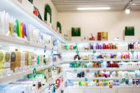 Various products on shelves at cosmetics store Blurred image.