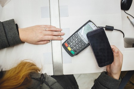 Wireless Paying by mobile phone. Close up top view transaction.