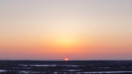 Crimson winter sun in zenith, clear sky. Natural vibrant cold colors
