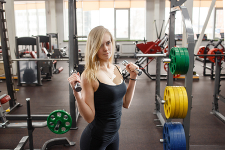 Young sporty woman in gym posing with dumbbells against a lot of gym simulators on background Stock Photo