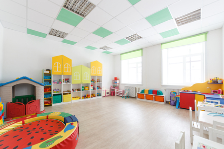 Spacious white game room in the kindergarten with toys, two large windows and tables for classes.
