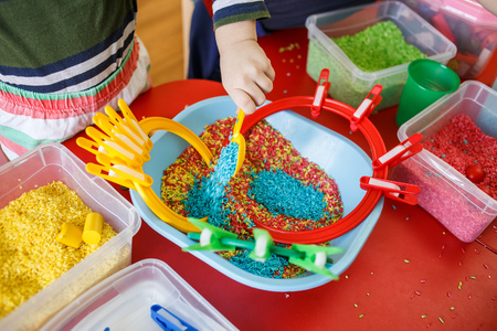 Toddlers playing with sensory bin with colourful rice on red table. 版權商用圖片