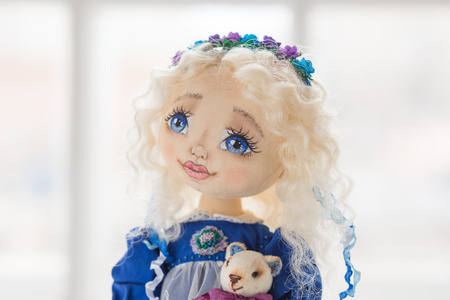 Portrait of textile handmade vintage doll with blue eyes, long blond hair in old blue textile dress with gentle print, in white shirt with purple boots on white background. She holding little textile teddy bear Stock Photo