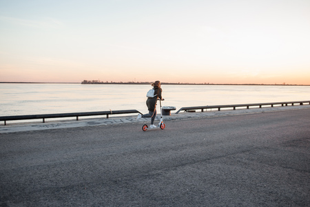 Joyful woman riding a kick scooter Zdjęcie Seryjne
