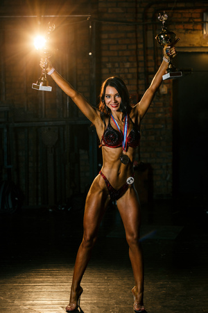 Attractive Athletic Woman Posing with Cups after Bodybuilding and Fitness Bikini Championships. Brutal Muscular Girl. Russian Regional Winner