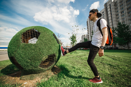 Stylish handsome man tourist is kicking the ball soccer ball of grass. Stock Photo