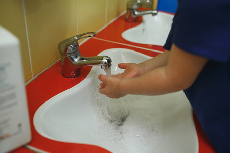 Child washing hands with soap in bathroom in kindergarten Reklamní fotografie